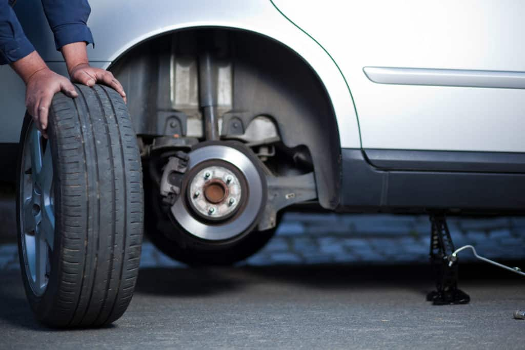 Replacing a customer's tire on the side of the road in Mays Landing
